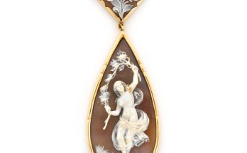 A shell cameo pendant/necklace a dancing nymph cameo suspended from a floral motif cameo